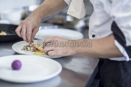 restaurantchef arrangiert speisen auf teller