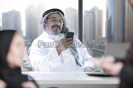 middle eastern businessman in office using