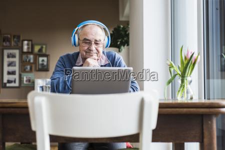senior man using laptop and headphones