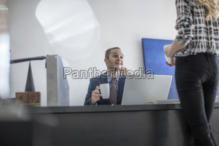 businessman at desk with cup of