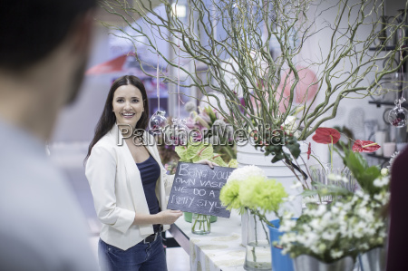 smiling young woman in flower shop