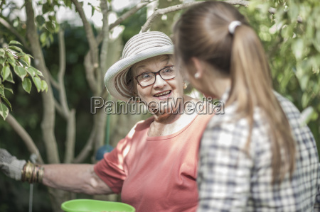 senior woman and teenage girl gardening