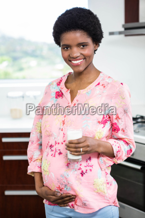 pregnant woman drinking a glass of