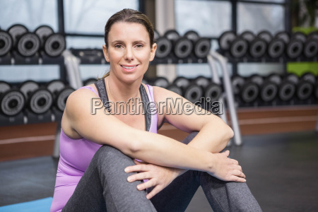 smiling woman sitting on mat looking