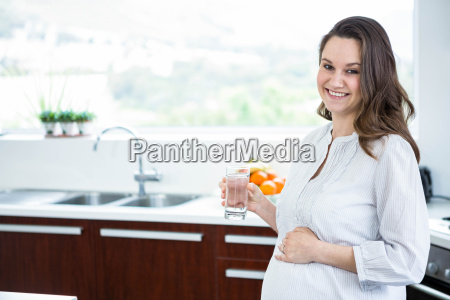 pregnant woman holding a glass of