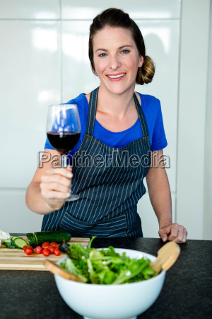 smiling woman preparing vegetables and drinking