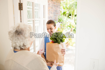 nice nurse bringing vegetables to old