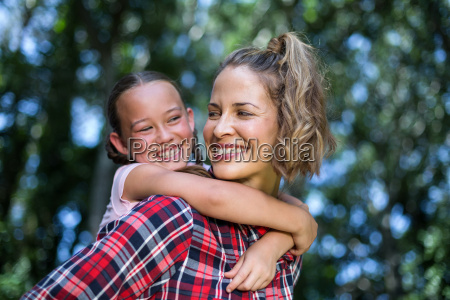 laughing mother carrying daughter while looking