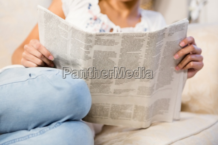 mid section of woman reading newspaper