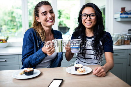 young female friends holding coffee mug