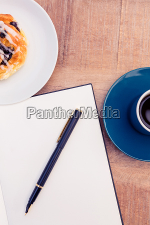 pen on notepad by food and