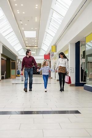 glueckliche familie zu fuss mit einkaufstueten