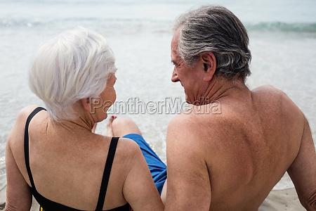 happy senior couple sitting on beach