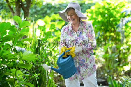 happy senior woman watering plants