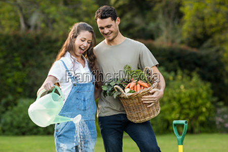 woman watering a plants while man