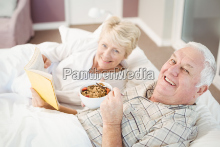 portrait of couple reading book while