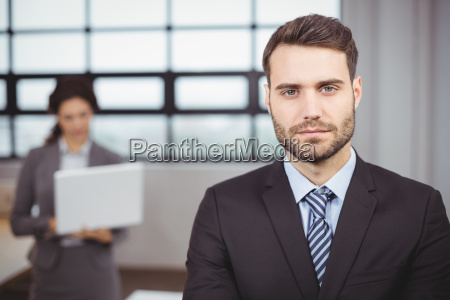 confident young businessman while colleague in