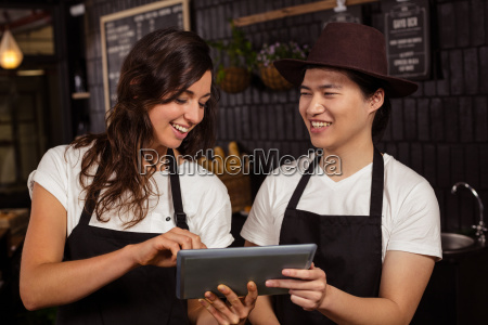 smiling co workers using tablet