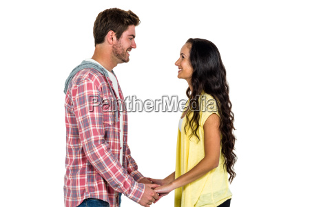 smiling couple holding hands and looking