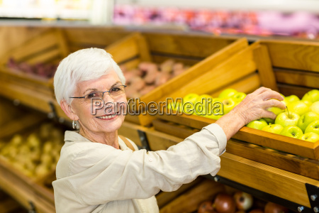 senior woman picking out a green