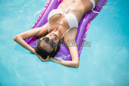 happy young woman relaxing on inflatable