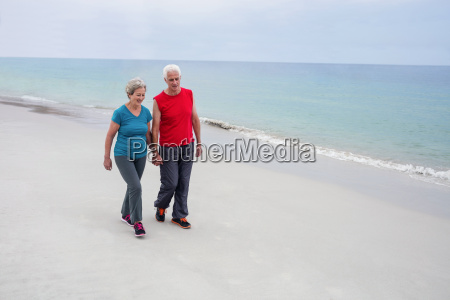 senior couple holding hands and walking