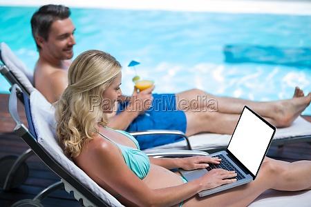 couple sitting on sun lounger near