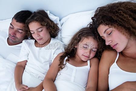 familie schlaeft gemeinsam auf bett