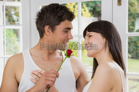 man offering a red rose to