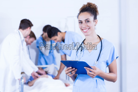 female doctor holding clipboard and smiling