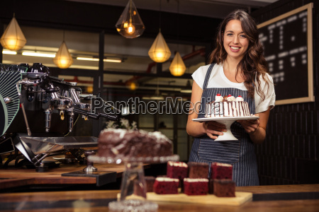 smiling barista holding plate with cake