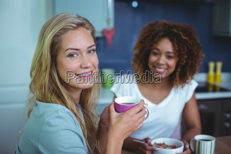woman drinking coffee with female friend