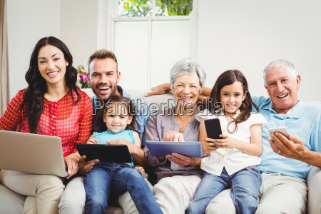 portrait of happy family holding technologies
