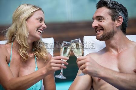 couple sitting on sun lounger toasting