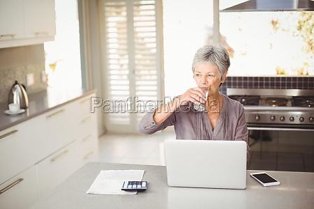 senior woman drinking water while sitting