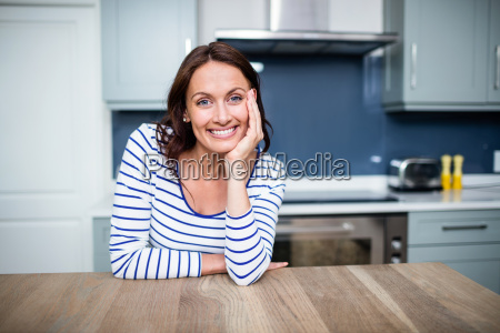 cheerful young woman sitting at table