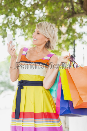 happy woman using smartphone with shopping