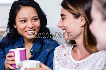 happy female friends with coffee cup