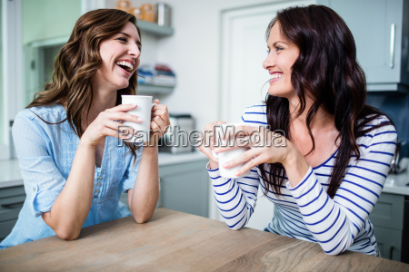 happy female friends holding coffee mugs