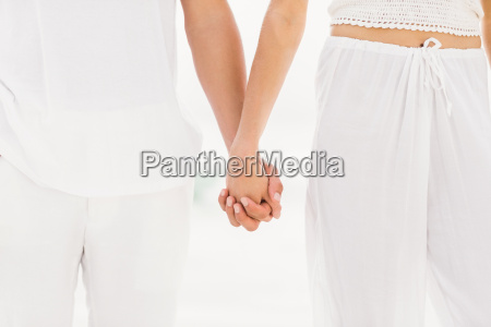 mid section of couple holding hand