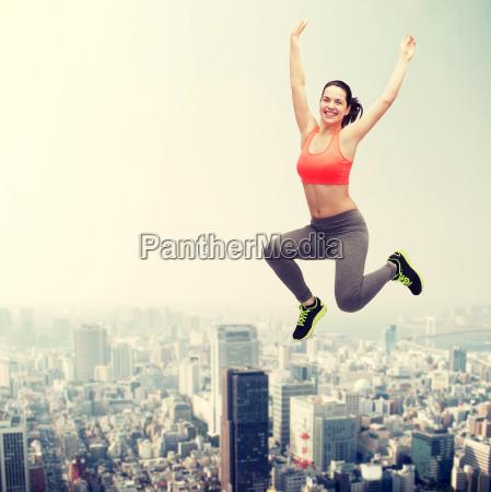 sporty teenage girl jumping in sportswear
