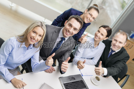 business team showing thumbs up in