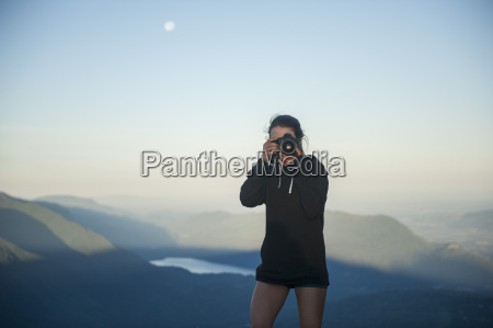 mid adult woman photographing with mountains
