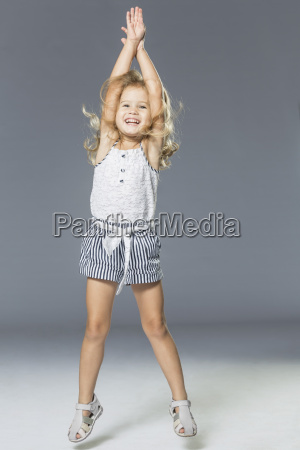 full length of playful girl jumping