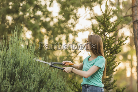 young woman cutting plants with pruning
