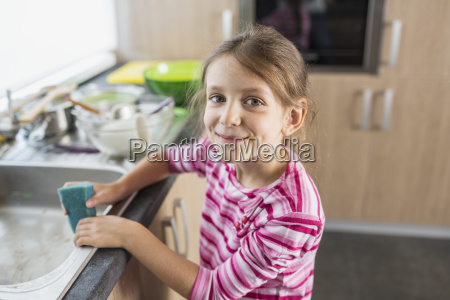portrait of smiling girl holding cleaning