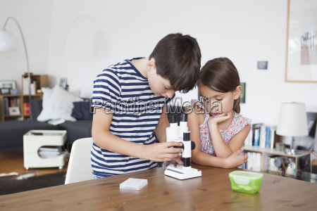 girl looking at brother using microscope