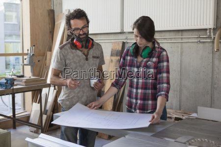male and female carpenters with blueprint