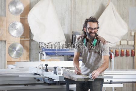 portrait of happy male carpenter measuring