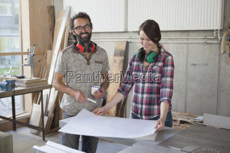 laughing male and female carpenters with